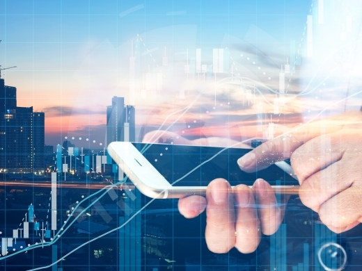 Business woman point finger to screen mobile phone and technical chart with metropolis city sunset background. (Shutterstock)
