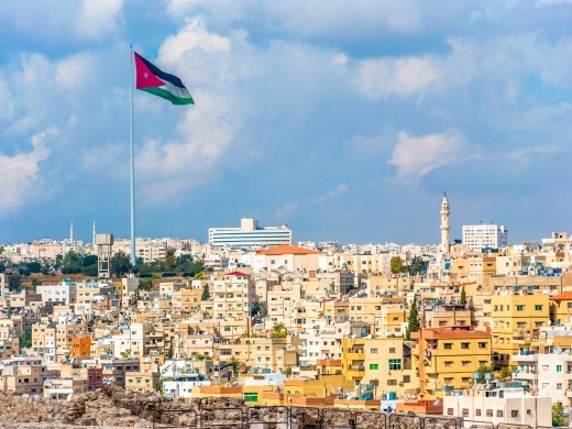 Jordan flag in Amman, cloudy sky background. (Shutterstock)
