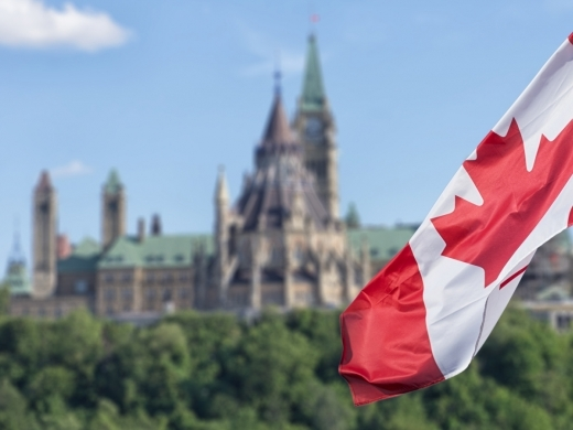 Canadian flag waving with Parliament Buildings hill and Library in the background. Source: DD Images/Shutterstock.com