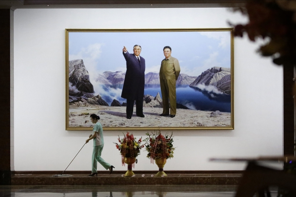 A hotel staff member mops the floor below a portrait of the late North Korean leaders Kim Il Sung, left, and Kim Jong Il on June 19, 2017, in Pyongyang, North Korea. (AP Photo/Wong Maye-E)