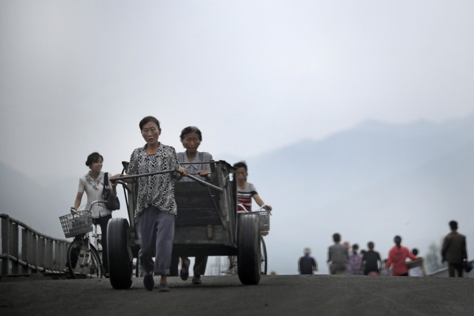North Korean women push their cart and bicycles over a bridge onJuly 21, 2017, in Hamhung, North Korea. Hamhung is the second largest city and the capital of South Hamgyong Province in North Korea. (AP Photo/Wong Maye-E)