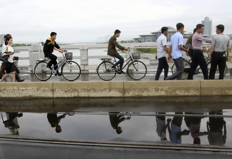 People are reflected in a puddle of water as they cross a bridge during the morning rush hour in Pyongyang, North Korea on June 15, 2018. (AP Photo/Dita Alangkara)
