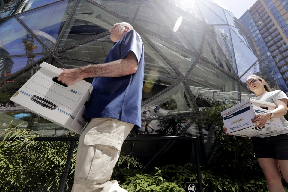 Outside of the Amazon headquarters in Seattle, volunteers carry boxes of petitions urging the tech giant to stop selling its face surveillance system, Rekognition, to the government. (AP Photo/Elaine Thompson)