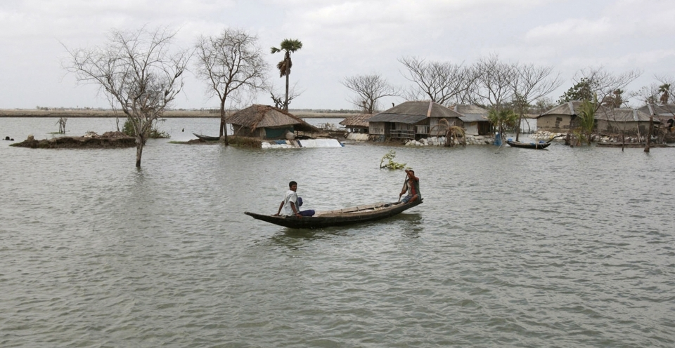 In this 2010 photo, a villager rows a boat past the Gabura village, an area affected by last year's cyclone Aila in Satkhira, about 175 kilometres from Dhaka, Bangladesh. (AP Photo/Pavel Rahman)