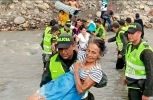 Elderly refugee carried by Colombian National Police across the river from Venezuela into Colombia/Wikimedia Commons