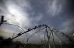 The barbed wire of a border fence by a makeshift camp near a border crossing at Idomeni, Greece (AP Photo/Gregorio Borgia)