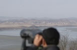 A visitor uses binoculars to see North Korea from the unification observatory in Paju, South Korea, Monday, January 1, 2018. (AP Photo/Lee Jin-man)