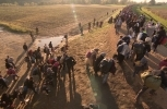 Refugees travelling as a large group over a barren landscape (Shutterstock)