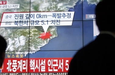 People walk by a screen showing the news reporting about an earthquake near North Korea's nuclear facility, in Seoul, South Korea, January 6, 2016. (AP Photo/Lee Jin-man)