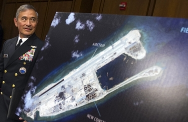In this Sept. 17, 2015, file photo, Adm. Harry B. Harris, Jr., commander of US Pacific Command, walks past a photograph showing an island that China is building on the Fiery Cross Reef in the South China Sea, as he prepares to testify on Capitol Hill in Washington before the Senate Armed Services Committee hearing on maritime security strategy in the Asia-Pacific region. (AP Photo/Cliff Owen)