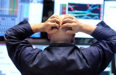 Specialist Justin Bohan holds his head as he works at his post on the floor of the New York Stock Exchange, Thursday Oct. 9, 2008. (AP Photo/Richard Drew)