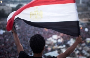 An Egyptian protester waves a flag in Tahrir square during a demonstration against Egypt's Islamist President Mohammed Morsi. (AP Photo/Manu Brabo)