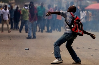 Amidst tear gas, a man throws stones against police officers during a protest in Port-au-Prince, Haiti, Sept. 14, 2011. (AP Photo/Dieu Nalio Chery)