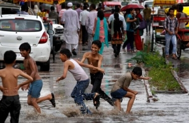 Children play in a water puddle left after a spell of rain in New Delhi, India. (AP Photo/Saurabh Das)