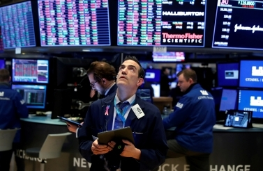 Traders work on the floor of the New York Stock Exchange (NYSE) as the building prepares to close indefinitely due to the outbreak of COVID-19. (Reuters/Lucas Jackson)