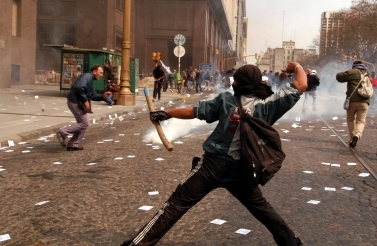 Demonstrators throw rocks in Buenos Aires to protest the visit of the then-IMF chief Rodrigo De Rato, Aug. 31, 2004 (AP Photo/DYN Liliana Servente)