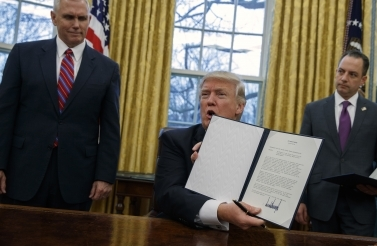 Donald Trump shows off an executive order withdrawing the US from the Trans-Pacific Partnership trade pact (AP Photo)