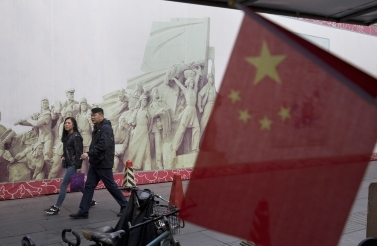 Two people walk by historic statue in China
