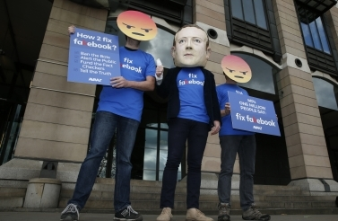 A protester wears a mask with the face of Facebook founder Mark Zuckerberg in London on April 26, 2018. (AP Photo/Alastair Grant)