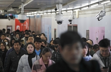 commuters walk by surveillance cameras installed at a walkway in between two subway stations in Beijing. (AP Photo/Andy Wong, File)