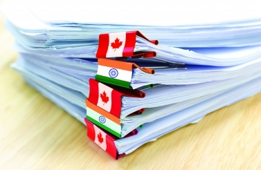 Documents held together using blinder-clips with the Indian and Canadian flags on them