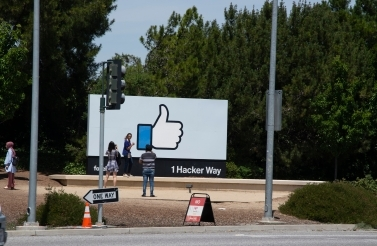 Passersby take photos with the sign at Facebook's headquarters. (Shutterstock)