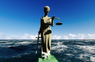 Scales of justice, ocean in background