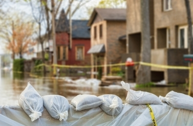 Sandbags with flooded homes in the background