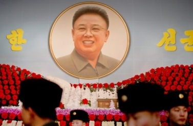 North Korean soldiers walk past a portrait of the late leader Kim Jong Il during a flower exhibition in Pyongyang, North Korea, Sunday, Feb. 16, 2014. (AP Photo/Vincent Yu)