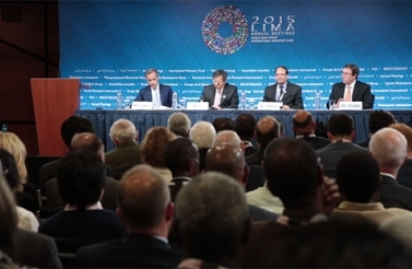Photo of four men speaking at IMF panel